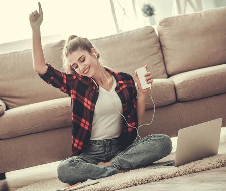 Het mooie meisje in vrijetijdskleding en oortelefoons luistert aan muziek gebruikend een slimme telefoon en glimlacht terwijl thuis het werken met laptop op de vloer Stockfoto