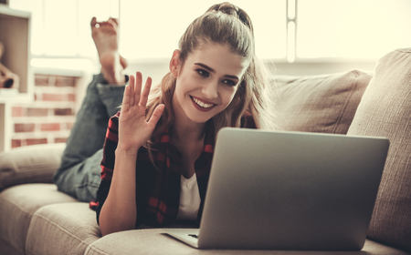 Beautiful girl in casual clothes is using a laptop, waving and smiling while lying on couch at home