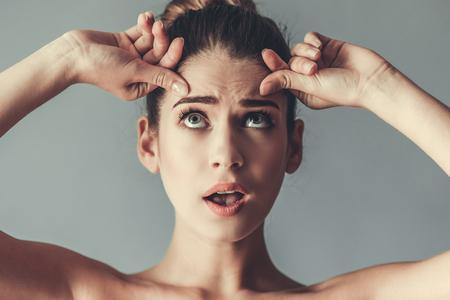 Portret van mooi meisje met blote schouders op zoek naar boven en aanraken van haar rimpels, op een grijze achtergrond