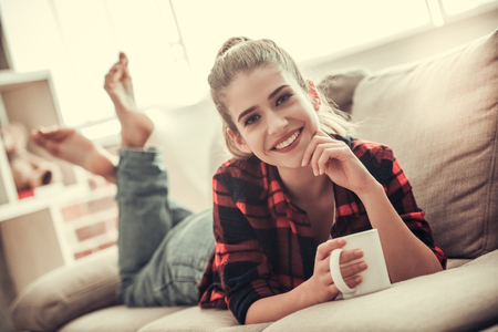 Beautiful girl in casual clothes is holding a cup, looking at camera and smiling while lying on couch at home 免版税图像