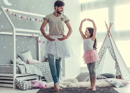 Cute little daughter and her handsome young dad in skirts are dancing and smiling while playing together in child's room