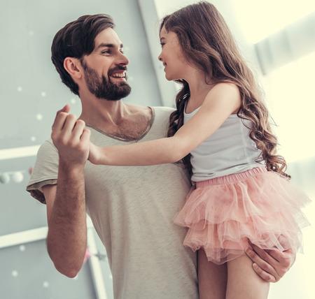 Jolie petite fille et son beau jeune papa dansent et sourient en jouant ensemble dans la chambre d'enfant Banque d'images - 81786717