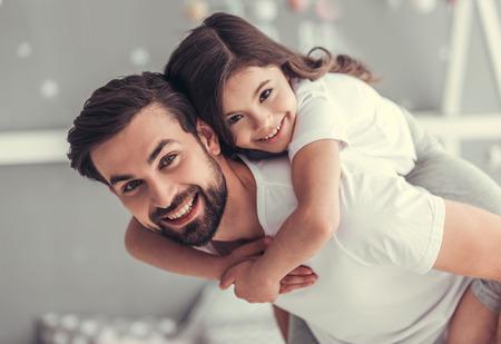 Der hübsche junge Vater und seine niedliche kleine Tochter spielen zusammen im Kinderzimmer. Mädchen sitzt Pickaback