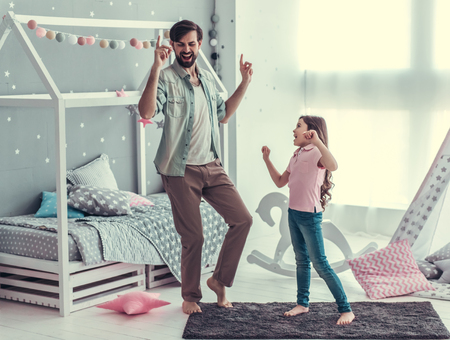 Cute little daughter and her handsome young dad are dancing and smiling while playing together in child's room