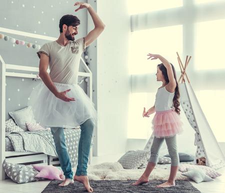 Nette kleine Tochter und ihr hübscher junger Vati in den Röcken tanzen und lächeln beim im Kinderzimmer zusammen spielen