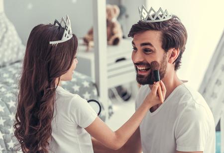 かわいい小さな娘と王冠で彼女のハンサムな若いお父さんは子供の部屋で一緒に遊んでいます。女の子は化粧彼女のお父さんをやっています。 写真素材