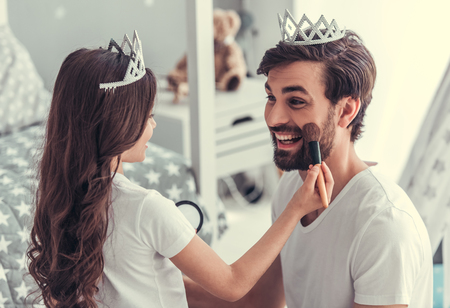 Cute little daughter and her handsome young dad in crowns are playing together in childs room. Girl is doing her dad a makeup Фото со стока