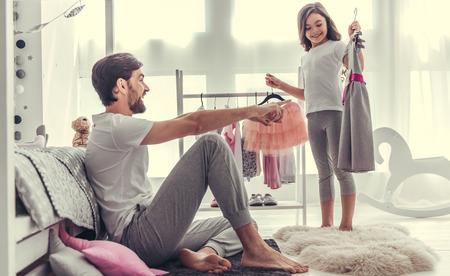 かわいい女の子は彼女のお父さんに美しい晴れ着を示すと笑みを浮かべながら彼女の部屋でプレイしています。