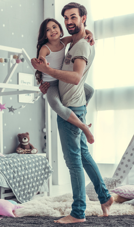 Cute little daughter and her handsome young dad are dancing and smiling while playing together in childs room