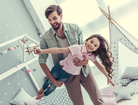 Little daughter and her handsome young dad are playing together in childs room. Girl is holding a toy plane and dad is holding his daughter