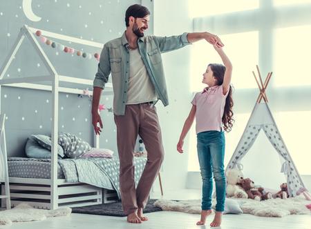 귀여운 작은 딸과 그녀의 잘 생긴 젊은 아빠 춤과 함께 웃고있는 동안 아이의 방에서 놀고
