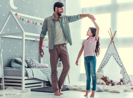 Cute little daughter and her handsome young dad are dancing and smiling while playing together in child's room Banco de Imagens - 81786789