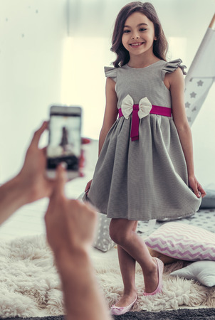 Dad is taking a photo of his cute little girl in dress using a smart phone, girl is smiling