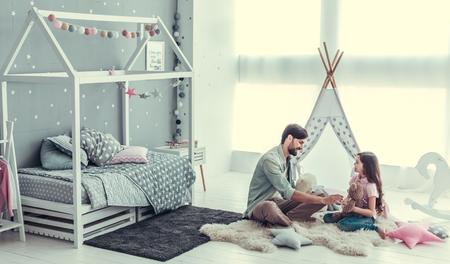 Schattige kleine dochter en haar knappe jonge vader zijn praten en glimlachen tijdens het spelen samen in de kinderkamer Stockfoto