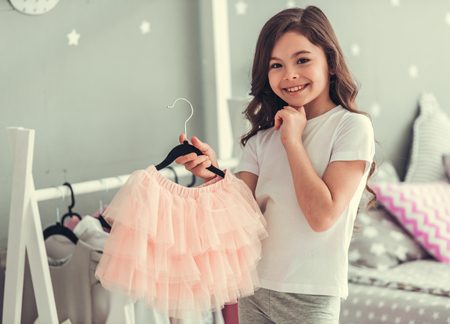 Cute little girl is holding a beautiful tulle skirt, looking at camera and smiling while playing in her room Banco de Imagens