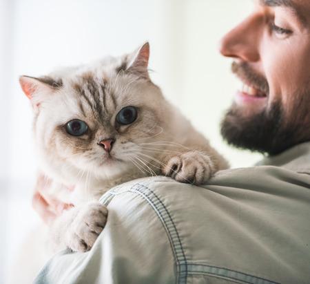 잘 생긴 젊은 남자가 그것을보고 웃고있는 귀여운 고양이를 잡고있다.