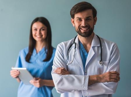 Schöne junge Ärzte sind Blick auf Kamera und lächelnd, auf blauem Hintergrund. Der Mensch steht mit gekreuzten Armen auf dem Vordergrund photo