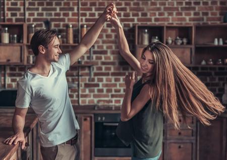 젊은 행복한 커플을 집에서 부엌에서 춤을