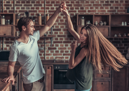 Young happy couple dancing at home in the kitchen