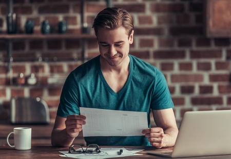 Junge Unternehmer arbeiten zu Hause. Verwenden Sie einen Laptop und trinken Sie Tee oder Kaffee.