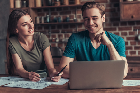 Family business. Young couple working with documents using laptop at home in the kitchen. Stockfoto