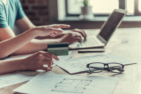 Familienbetrieb. Junges Paar arbeitet mit Dokumenten mit Laptop zu Hause in der Küche.