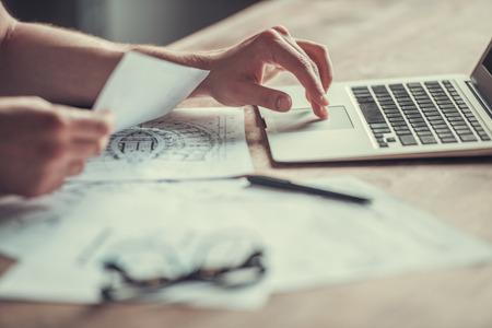 Nahansicht. Junge Unternehmer arbeiten zu Hause. Verwenden Sie einen Laptop und trinken Sie Tee oder Kaffee. Lizenzfreie Bilder