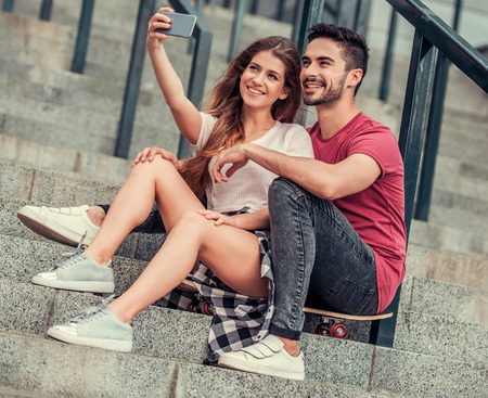 Stylish junges Paar macht selfie mit einem Smartphone und lächelnd beim Sitzen auf dem Skateboard auf Treppen im Freien