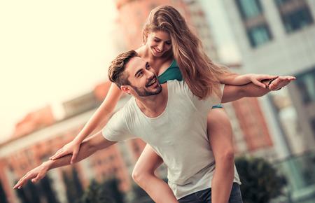 Stylish junges Paar lächelt beim Gehen in der Stadt. Mädchen sitzt Pickaback