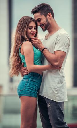 Das stilvolle junge Paar umarmt und lächelt beim Gehen in der Stadt