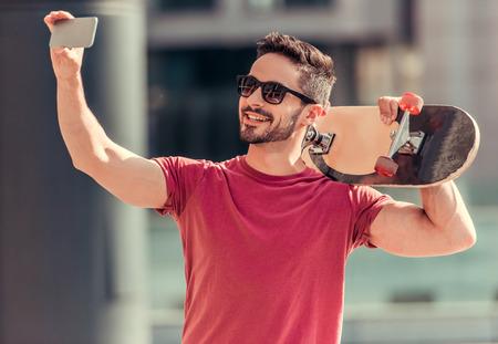 Stilvolle Kerl in Sonnenbrille hält ein Skateboard, Selbstständig mit einem Smartphone und lächelnd beim Gehen im Freien