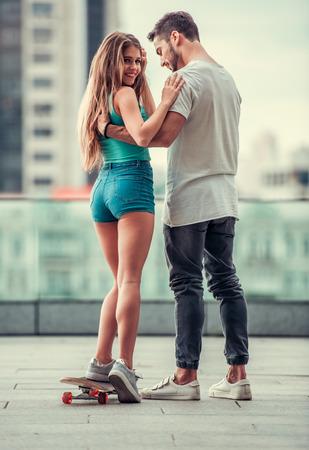 Stilvolles junges Paar geht in der Stadt, in voller Länge. Guy lehrt seine Freundin auf Skateboard fahren