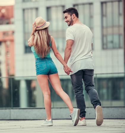 Stylish junges Paar hält Hände, reden und lächelnd beim Gehen in der Stadt, in voller Länge
