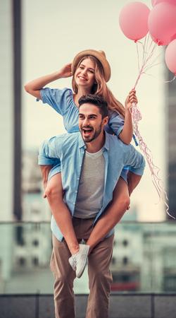 Romantisches Paar macht Spaß beim Gehen in der Stadt. Mädchen sitzt Pickaback und hält Ballons Lizenzfreie Bilder