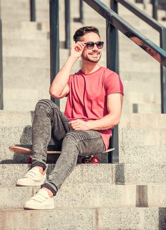 Stilvolle Kerl in Sonnenbrille schaut weg und lächelt beim Sitzen auf seinem Skateboard auf Treppen im Freien Lizenzfreie Bilder