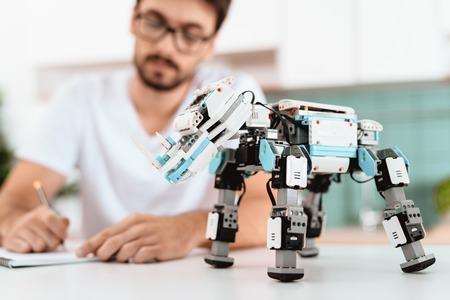 ある男性が台所でロボットをプログラミングしています。近くにはロボット自体とグレーのノートパソコンがあります。