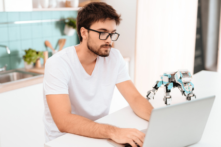 A man is programming a robot in the kitchen. He works on a gray laptop. The robot stands next to the table. Stock Photo