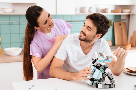 A man collects a robot in the kitchen. The girl gently hugs him from behind. They are smiling.