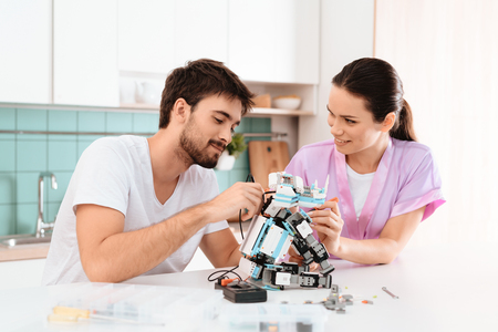 The guy is doing the robot in the kitchen. His girlfriend is standing next to him and helping him. Stock fotó