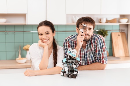 A guy and a girl are posing in the kitchen. They lean on the table. A robot sits next to them. They are smiling.