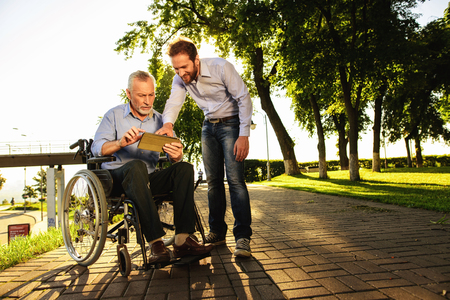 Old man in a wheelchair and a man looking at something in a tablet walking in the park. They are happy