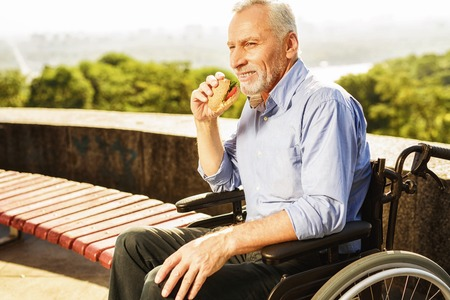 The old man is sitting in a wheelchair and eating. He smiles