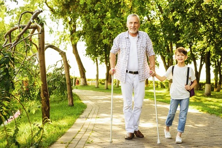 A boy and an old man on crutches are walking in the park. The boy is holding the old mans hand