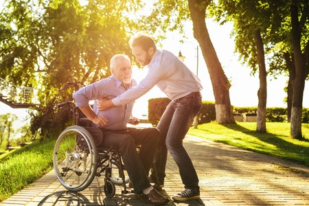 The old man tries to get out of the wheelchair. on crutches. His son helps him