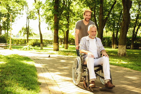 A pensioner on a wheelchair and his adult son are walking around the park. They are happy and have fun Banco de Imagens