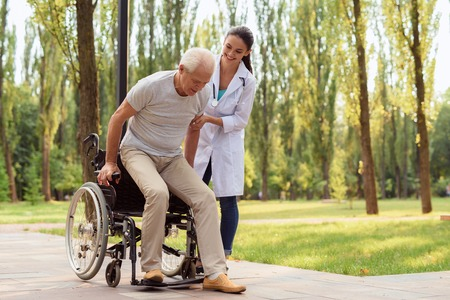 The doctor helps the patient to get up from the wheelchair and walk Stock Photo