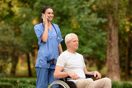 Nurse and old man sitting in a wheelchair in the park. Nurse talking on mobile phone