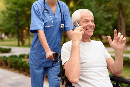 Happy old man in a wheelchair talking on a mobile phone Stock Photo