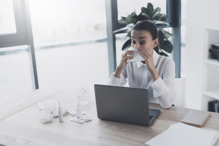 Sick woman sitting at her workplace in the office. She blow her nose at the workplace
