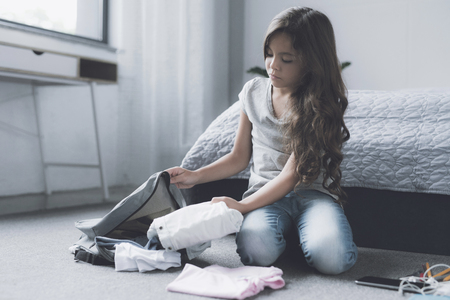 A sad black-haired girl sits on the floor near the bed and collects things in a gray backpack Stock Photo